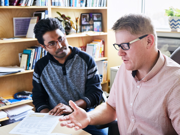student and professor working together in office