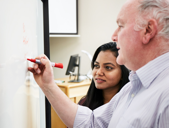 student standing with professor at white board
