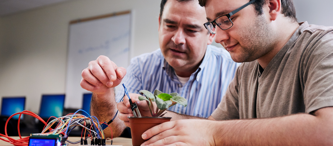 student and professor working together on plant project