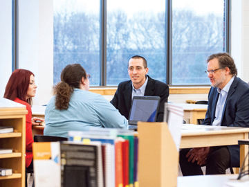 students and professors conversing in library