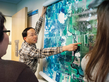 professor pointing to large map on wall