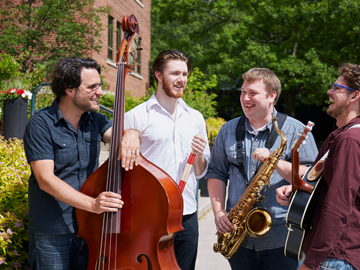 students standing in group holding instruments outside