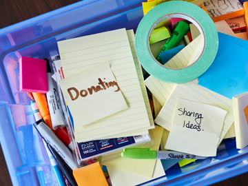 plastic bin filled with supplies, post-it notes with the words