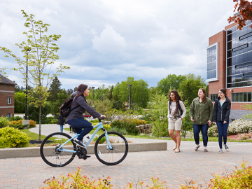 student riding bike in one direction with three students walking opposite
