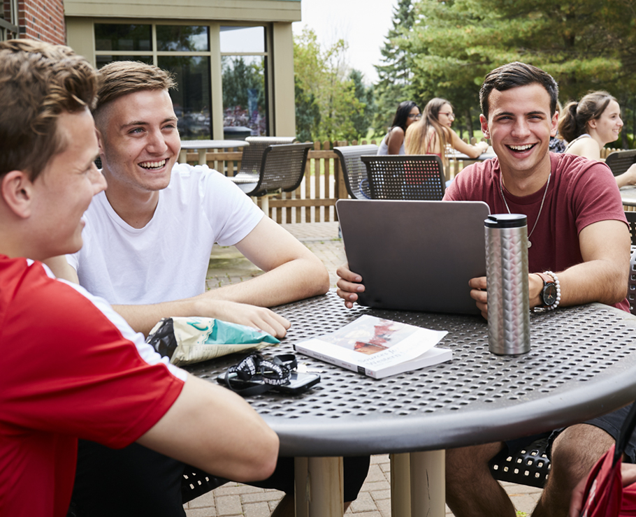 students laughing outside on campus
