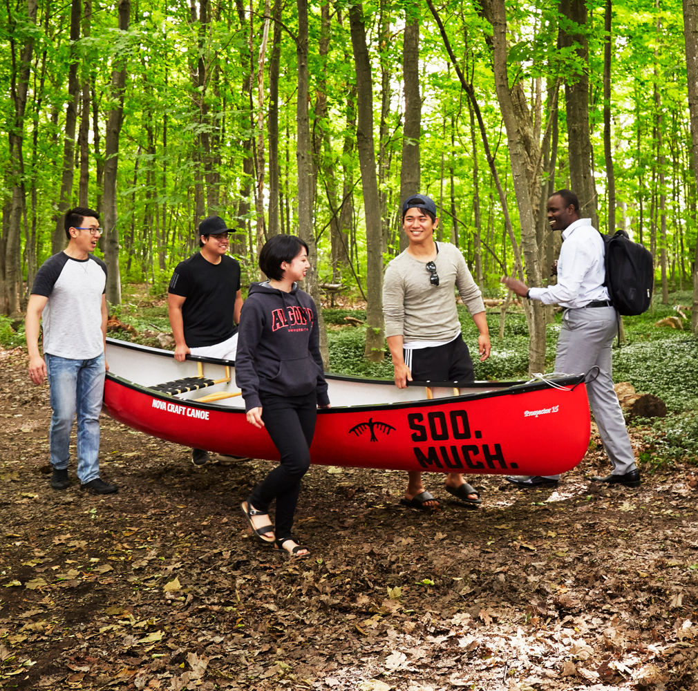 students carrying canoe through forest