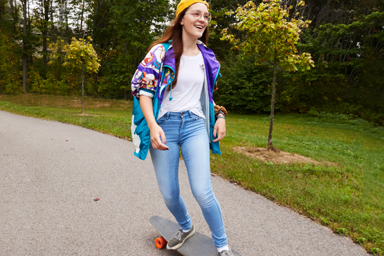 student riding longboard down path