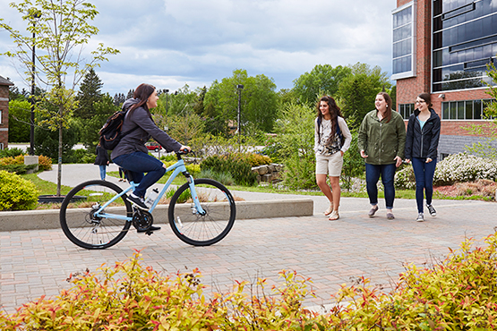 students walking and cycling through campus