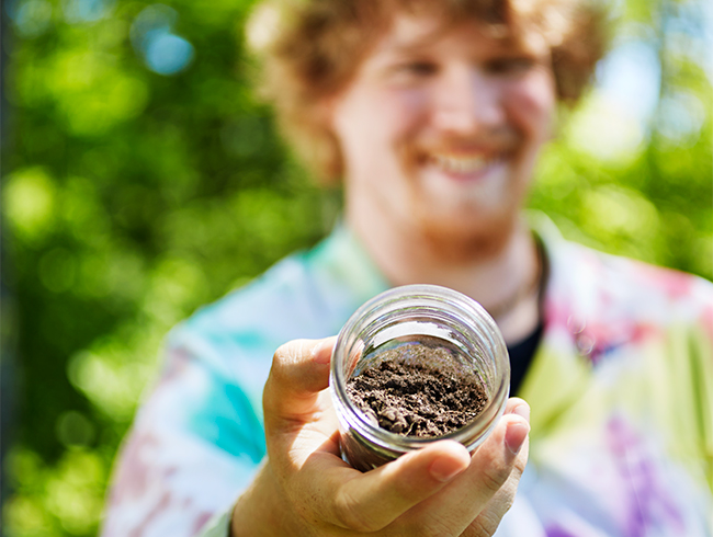student holding jar of earth