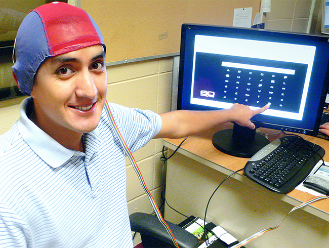 student in computer lab wearing cap