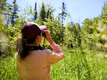 student looking into binoculars in the forest