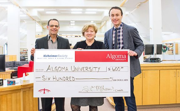 officials standing with large cheque for six hundred dollars