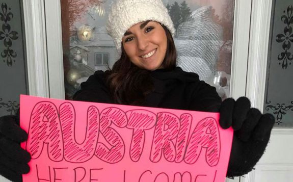 student holding austria here i come sign