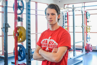 student standing with arms crossed in gym