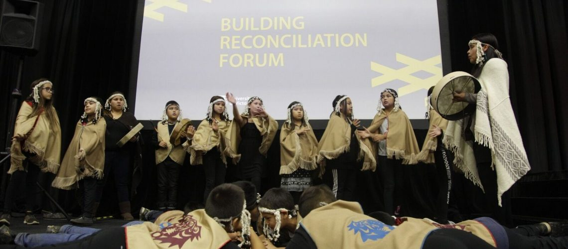 students performing on stage at building reconciliation forum