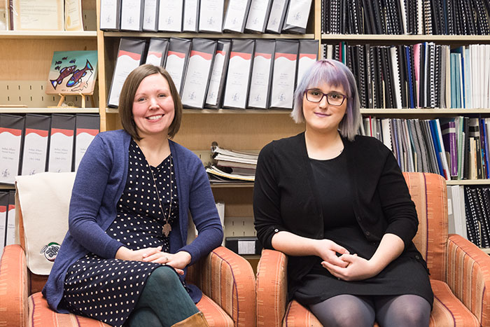 staff sitting and smiling in library
