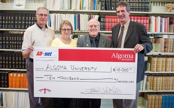 officials standing with large cheque for ten thousand dollars