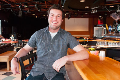 student smiling while sitting at bar