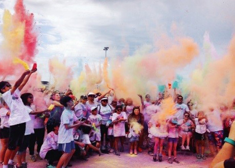 student a the colour run throwing coloured powder in the air