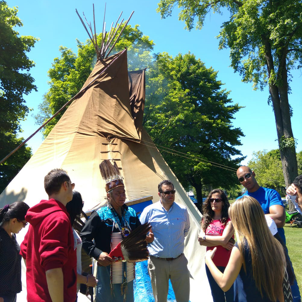 students speaking with chief next to a tipi