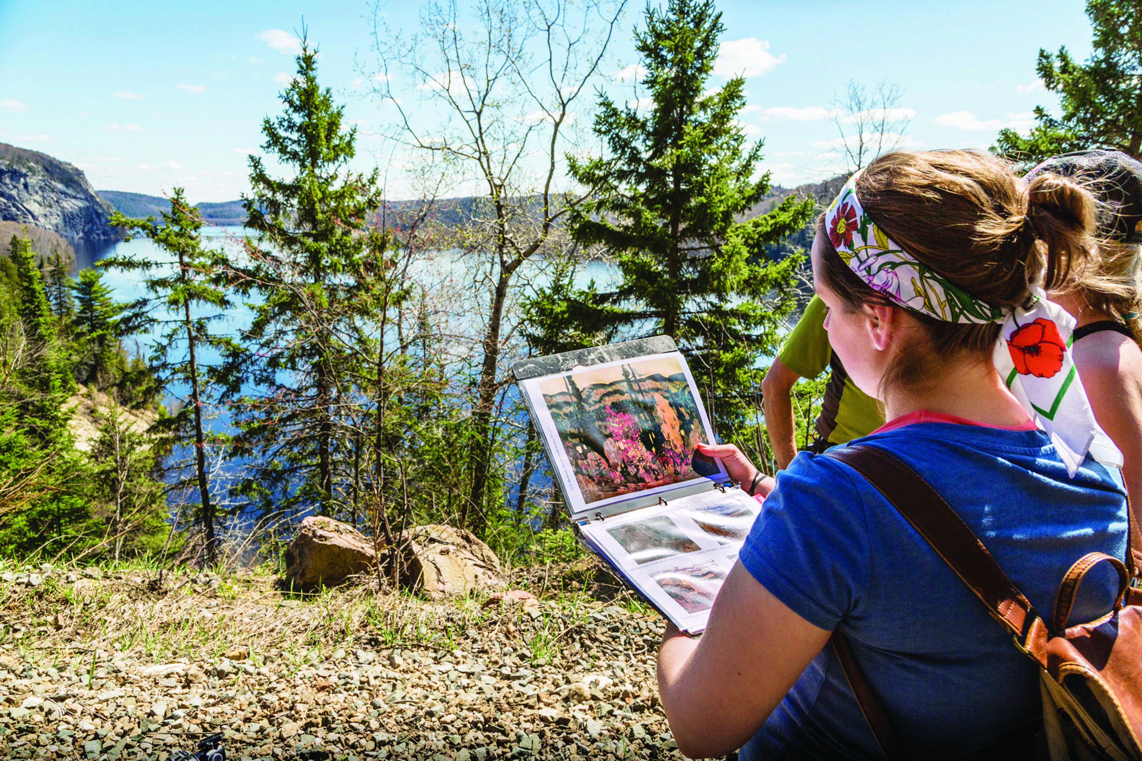 student outdoors looking at group of 7 painting overlooking Lake Superior
