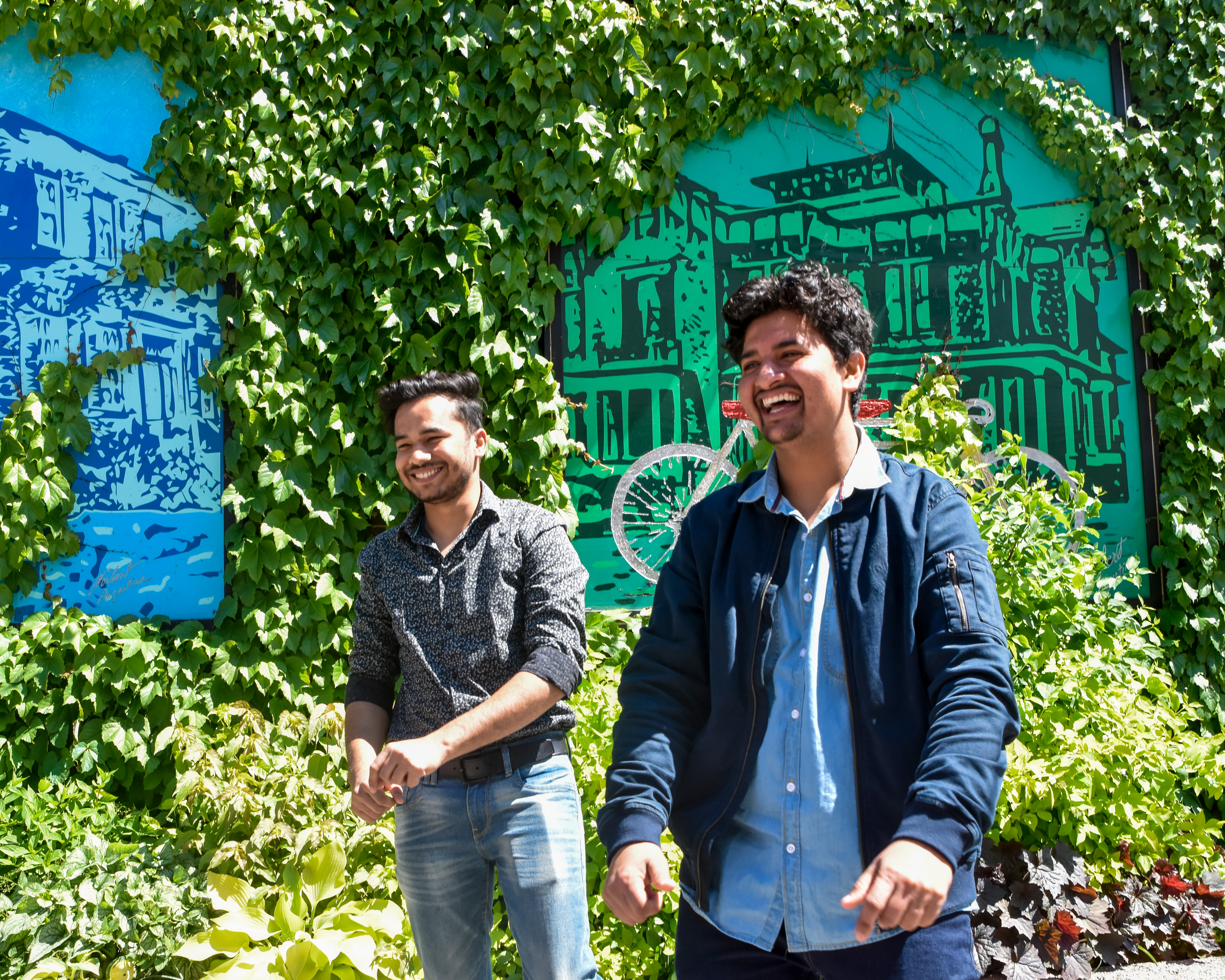 two students laughing outdoor near decorated wall in Brampton