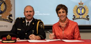 police chief and Algoma U president signing document