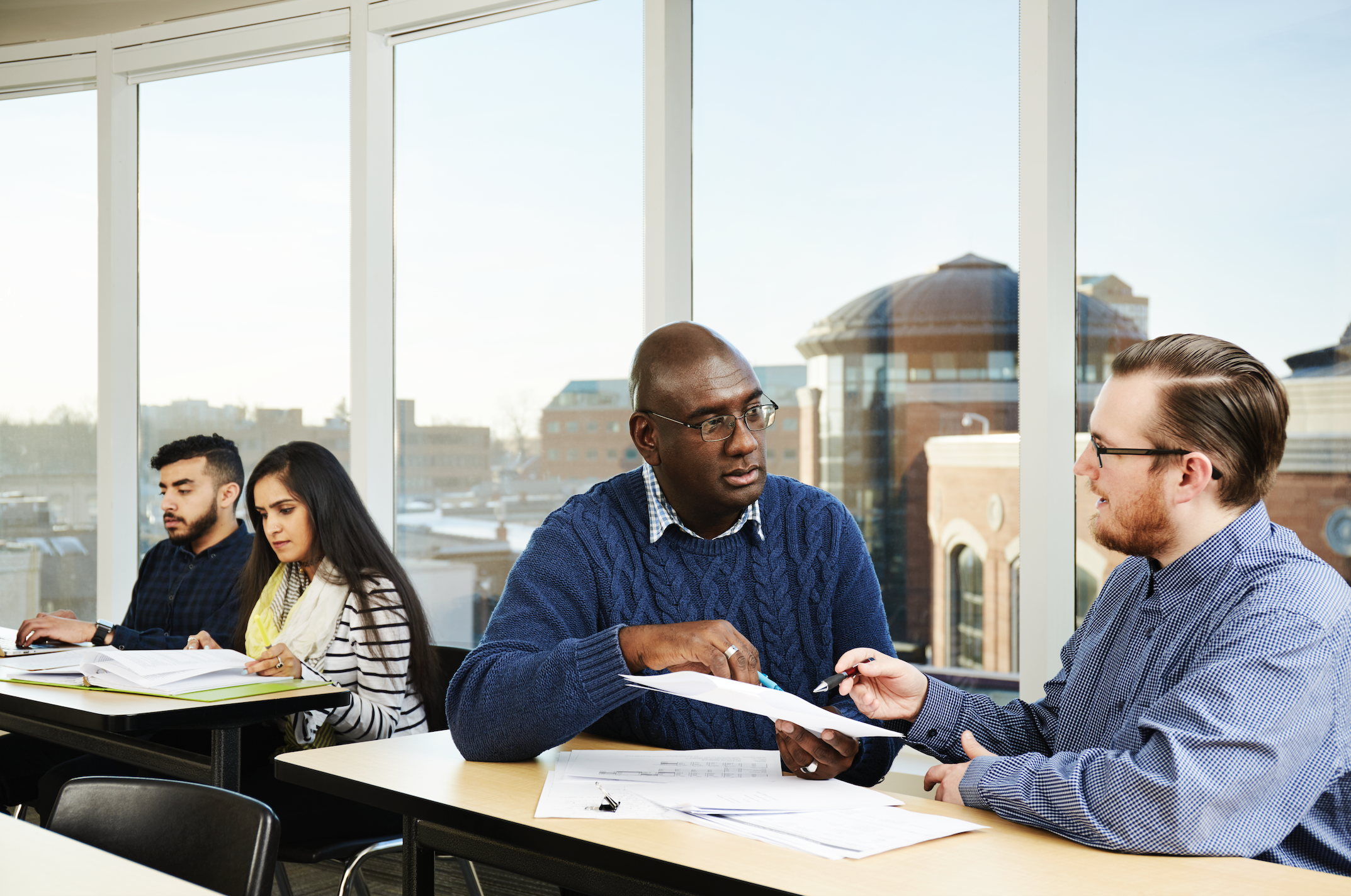 students in class discussing with faculty