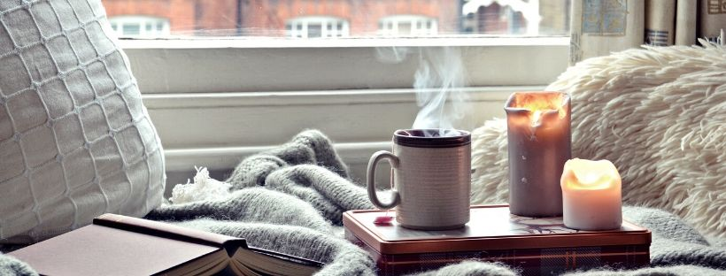 coffee mug, text book and two candles on a table